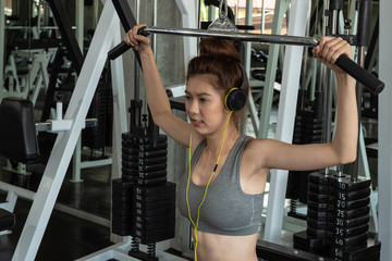 Portrait of young woman using weight lifting equipment to build a massive chest and arm at indoor sport gym , bodybuilder concept.