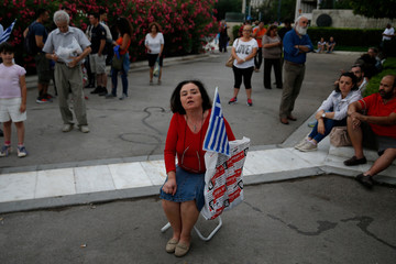 A woman takes part in a demonstration against the agreement reached by Greece and Macedonia to resolve a dispute over the former Yugoslav republic's name, in Athens