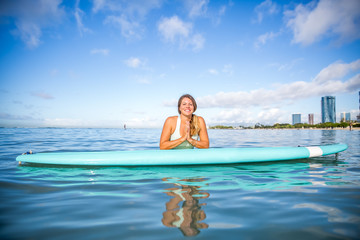 Athlete in gratitude on her paddle board in Hawaii