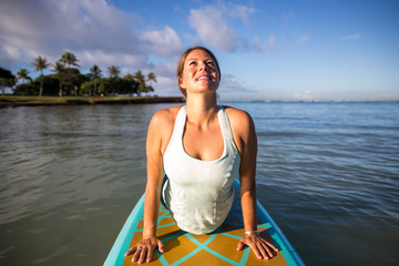 Pretty woman in upward dog pose doing SUP Yoga on the water