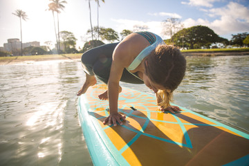 Sunny morning sun flare moment of a pretty young woman in SUP Yoga practice Shoulder-Pressing Pose in Ala Moana Hawaii