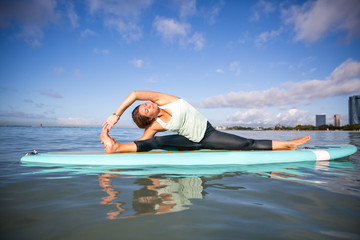 Athletic young woman in SUP Yoga practice side bend Pose in Ala Moana Hawaii
