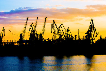 Silhouette of a crane. Cranes at the port. Silhouette of harbor at sunset. Sea port. Sunset at the port.
