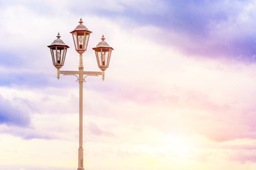 Old street lamp on a background of cloudy sky. Soft colors. Beautiful background. Fotomurales