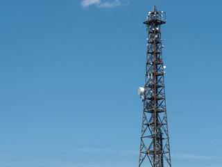 Steel lattice communications tower with an array of dishes for transmission and reception