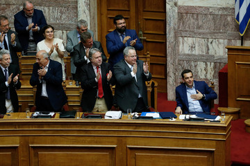 Greek Prime Minister Alexis Tsipras is applauded by lawmakers after his speech during a parliamentary session before a vote following a motion of no confidence by the main opposition in dispute over a deal on neighbouring Macedonia's name, in Athens
