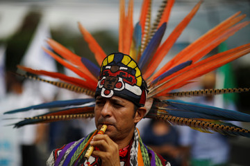 A man dressed in an indigenous costume participates in a protest against privatization of water in San Salvador