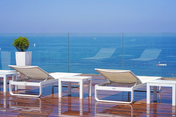 Two loungers, standing on a wooden floor on the background of the sea. View from the pool to the terrace of the hotel suite rooms.