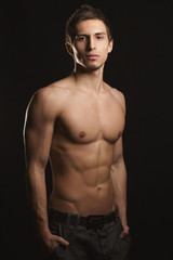 Shirtless, fitness shaped muscular men with perfect sporty body only in jeans with arms in a pockets posing at black background