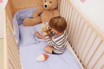 Ein zweijähriger Junge in seinem Kinderbett