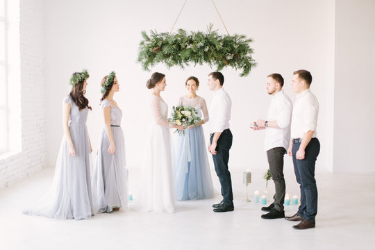 Young fashionable lovely couple together with bridesmaids and groommen with speech master of wedding ceremony against decor pine arch on wedding anniversary and marriage proposal.