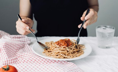 young attractive beautiful girl woman eating Italian food a plate of pasta with sugo, lifestyle. Italian food concept, , home made food, cooking at home,