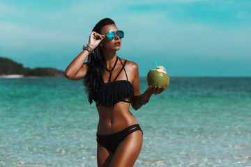 Beautiful sexy amazing young woman on the beach, excellent time, tanned radiant skin, long hair, black bikini, mirror sunglasses, fashion, glamor, vacation on a tropical island,  low key photos