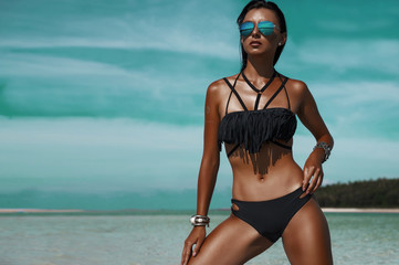Beautiful bohemian styled woman, tanned girl at the beach, sexual black bikini, wet hair, holiday time, simmer fashion woman at tropical island,  stylish silver accessories, luxurious tanned body