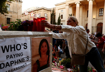 A woman places candles on the makeshift memorial to assassinated investigative journalist Daphne Caruana Galizia during a vigil and demonstration marking eight months since her murder in a car bomb, in Valletta