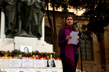 Megan Mallia, niece of assassinated investigative journalist Daphne Caruana Galizia, addresses protestors during a vigil marking eight months since her murder in a car bomb, at a makeshift memorial on the Great Siege monument in Valletta
