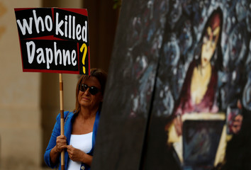 A woman holds a poster next to an artwork depicting assassinated investigative journalist Daphne Caruana Galizia during a vigil and demonstration marking eight months since her murder in a car bomb, in Valletta