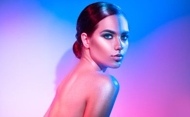 High fashion model girl in colorful bright sparkles and neon lights posing in studio. Portrait of beautiful woman, trendy glowing make-up. Art design colorful make up. Glitter vivid neon makeup