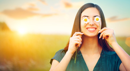 Beauty joyful girl with daisy flowers on her eyes enjoying nature and laughing on summer field. Beautiful young woman having fun Fotobehang