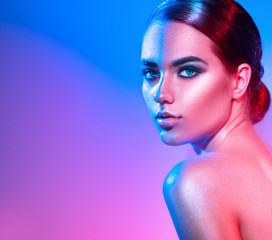 High fashion model girl in colorful bright sparkles and neon lights posing in studio. Portrait of beautiful woman, trendy glowing make-up. Art design colourful make up. Glitter vivid neon makeup