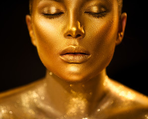 Golden skin woman face. Fashion art portrait closeup. Model girl with holiday golden glamour shiny professional makeup. Gold jewellery, jewelry, accessories. Beauty gold metallic body, lips and skin