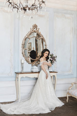 Beautiful bride, charming model brunette girl in stylish wedding lace dress with naked shoulders adjusts her dress and posing near the mirror at luxury vintage interior
