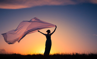 Female silhouette holding silk cloth blowing in the wind. People freedom and serenity concept.