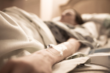 Unrecognizable sick woman lying in hospital bed.