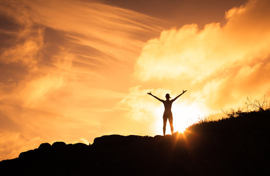Female standing on a mountain with her arms up in the air. Happiness, motivation and feeling good concept.