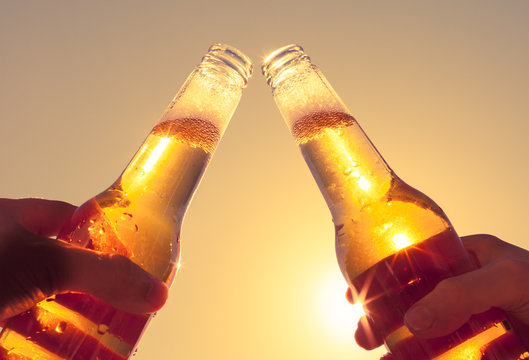 Cheers with ice cold beer on hot summer day. Party and celebration concept.