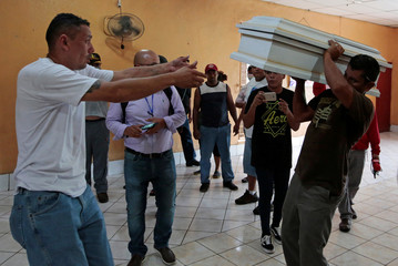 A man receives a coffin containing the body of a child who died after a building caught fire, in Managua