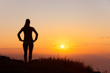 It's a new day concept. Young female standing watching the sunrise.