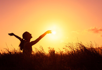 Young woman in a beautiful nature sunset setting raising her arms up in the air. Happiness freedom and joy concept.