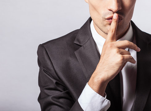 Man saying hush be quiet with finger on lips gesture isolated on gray wall background. Top secret concept.