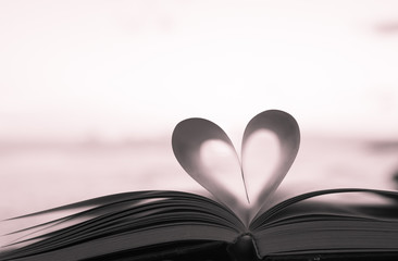 Close up heart shape from paper book on sand in the beach with vintage filter blur background