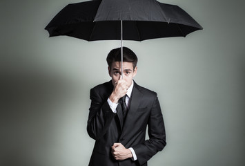Expressive man in suit holding umbrella over head.