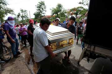 People carry a coffin containing the body of a person who died after a building caught fire, in Managua