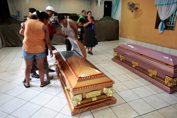 Family members and friends look into the coffin of a person who died after a building caught fire, in Managua