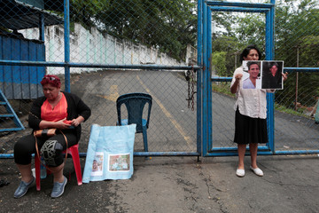 Women, one chained to the fence, are seen outside a jail demanding their sons to be released after they were detained during recent protests, in Managua