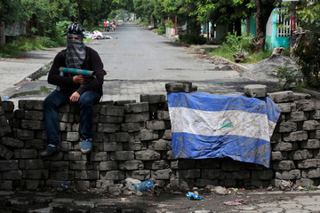 A man holding a homemade mortar sits on a roadblock in Managua