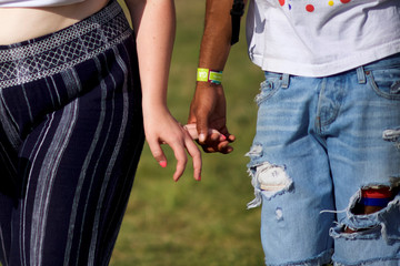 A couple holds hands on the third day of the Firefly Music Festivalin Dover, Delaware U.S.