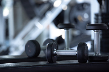lose up of modern dumbbells equipment in the sport gym , gym equipment concept.