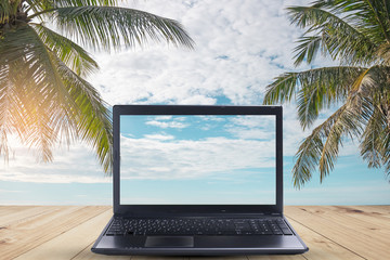 A laptop  on wood table in the sea beach with coconut tree.