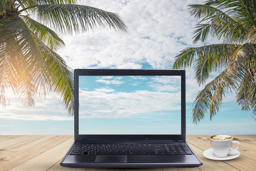 A laptop with coffee cup  on wood table in the sea beach with coconut tree.