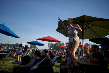A woman dances on a picnic table as Lil Wayne performs on the third day of the Firefly Music Festival in Dover, Delaware U.S.