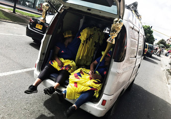 People transport shirts of the Colombian National soccer team and replicas of the World Cup trophy on a van to sell along a street in Bogota, Colombia