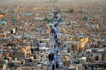 """People visit the """"Valley of Peace"""" cemetery during Eid al-Fitr as they mark the end of the fasting month of Ramadan, in Najaf"""