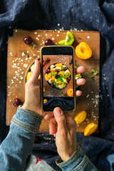 Hands taking smartphone photography of food. Phone photo of fruit salad in bowl on wooden board. For social media or blogging. Healthy sweet dessert for breakfast. Raw vegan vegetarian healthy food