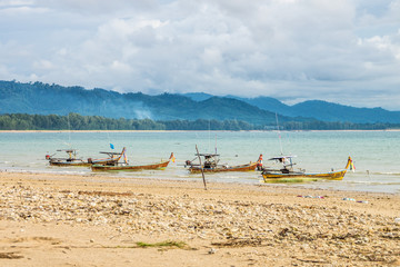 Four traditional Thai fishing boats anchored on Than Tawan beach in Thailand. They are motorboat and made of wood.