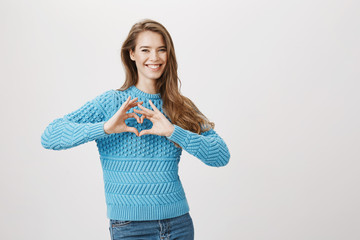 Studio portrait of emotive lovely girlfriend showing heart gesture and smiling broadly while expressing her attitude to man she loves, standing over gray background. Friend got her great present